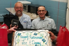 Dan Hynes (30-yrs) and Joe Roche (44-yrs) pose with their retirement cake on their last days of service.